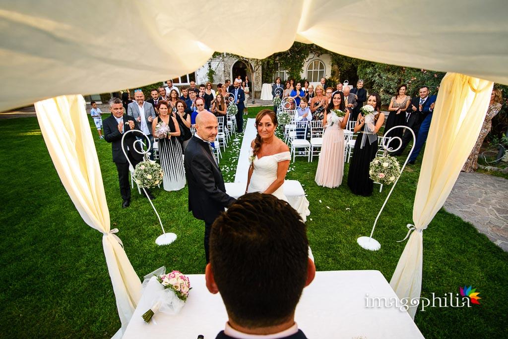 Veduta, dalle spalle del celebrante, degli sposi e degli invitati durante la celebrazione del matrimonio a Villa Pocci