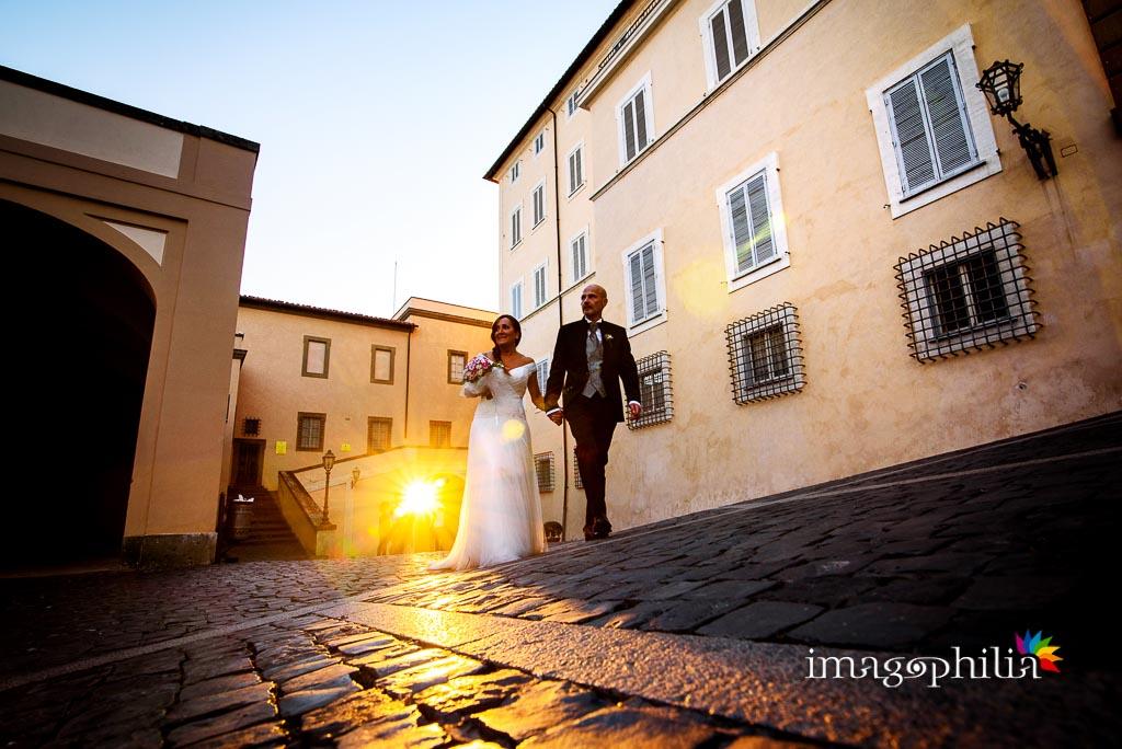 Gli sposi entrano a Castel Gandolfo con la luce del tramonto che filtra dalla porta del borgo