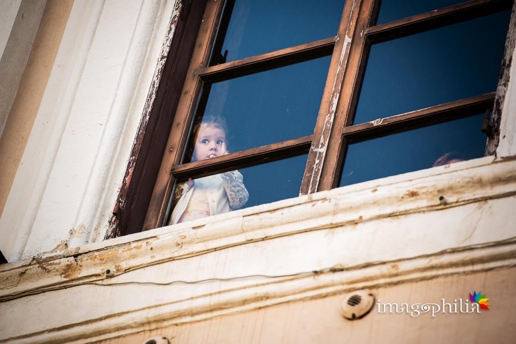 La piccola damigella scruta alla finestra l'arrivo della sposa