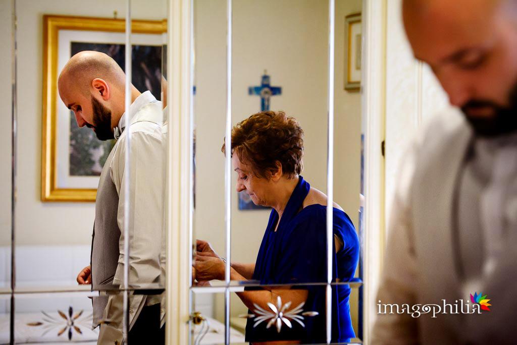 Lo sposo con la mamma, riflessi nello specchio, durante la preparazione
