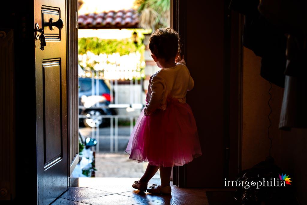 La piccola nipotina dello sposo lo guarda mentre esce da casa