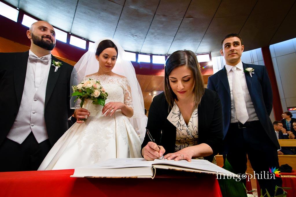 La testimone della sposa firma il registro accanto all'altro testimone