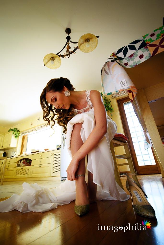 La sposa indossa le scarpe prima di uscire da casa