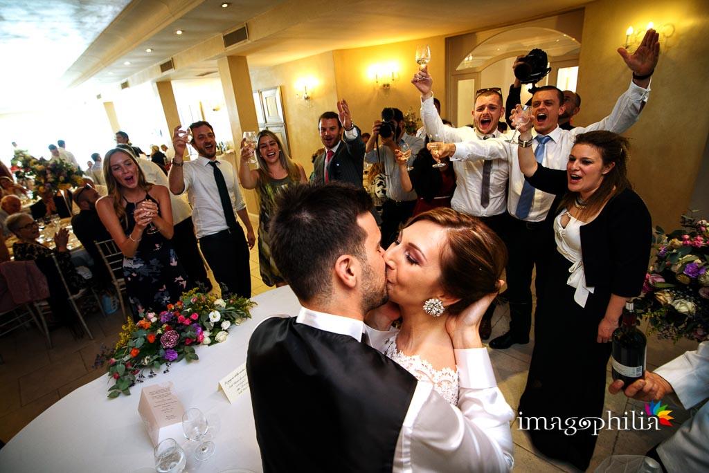 Gli sposi si baciano, in mezzo al tifo degli invitati, alla Casina di Poggio della Rota