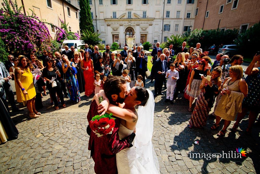 Bacio tra gli sposi dopo il lancio del riso nel chiostro della Basilica di Santa Cecilia in Trastevere a Roma