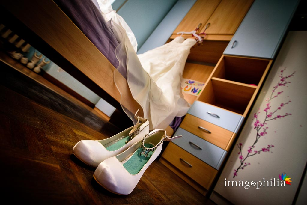Le scarpe della sposa e, sullo sfondo, il suo vestito
