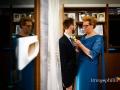 La mamma aggancia la boutonnière al bavero della giacca dello sposo