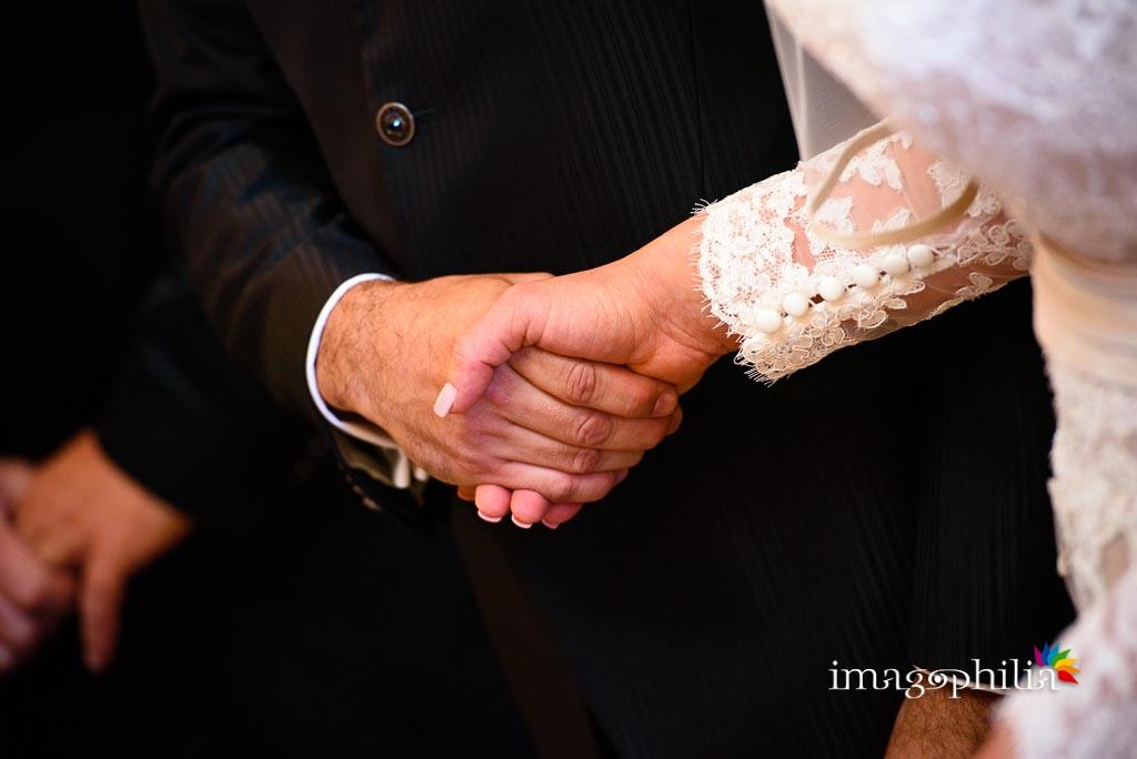 Gli sposi si stringono le mani durante il matrimonio nella Chiesa Aeroportuale di Guidonia Santa Maria di Loreto