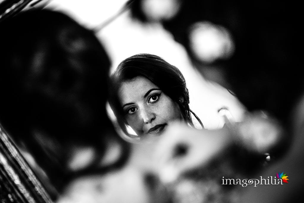 La sposa si specchia durante la preparazione a casa