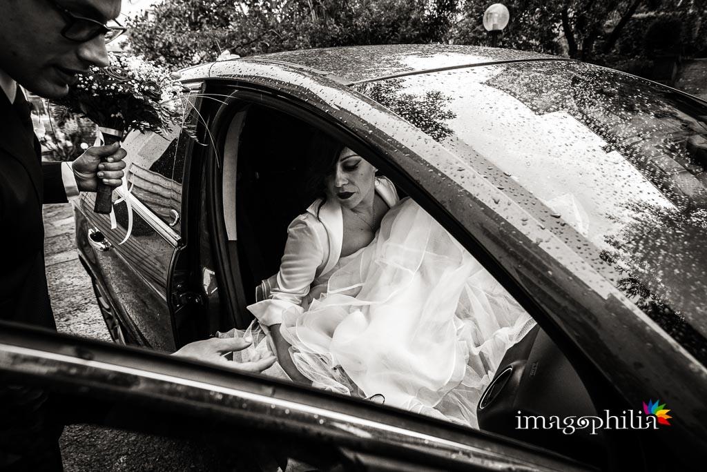 La sposa sale nella sua macchina bagnata per andare in chiesa