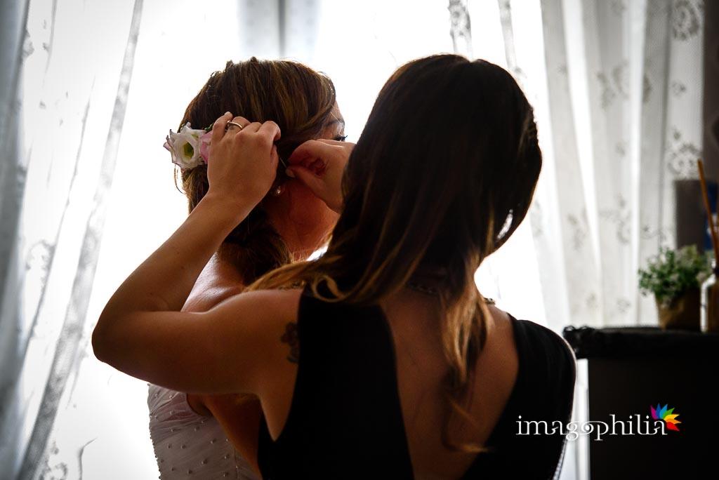 La figlia della sposa la assiste negli ultimi ritocchi prima di uscire da casa