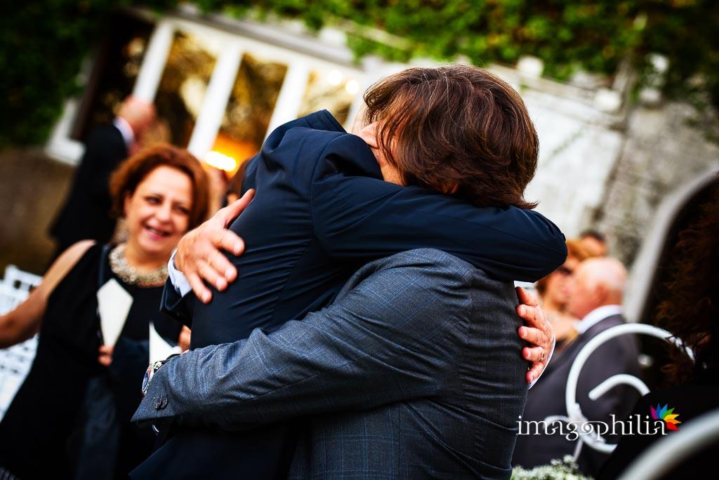 Abbraccio tra lo sposo e un suo amico al termine del matrimonio a Villa Pocci