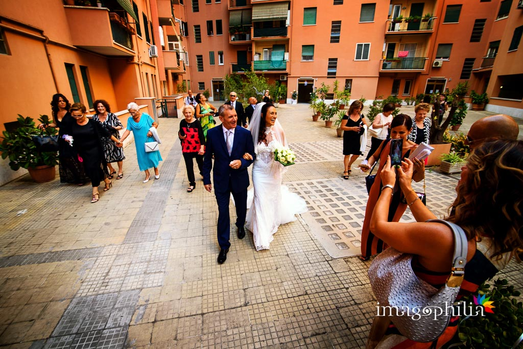 La sposa, accompagnata dal padre, esce di casa passando per il mega cortile