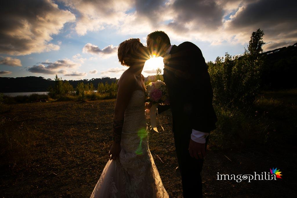 Bacio tra gli sposi in riva al lago controluce