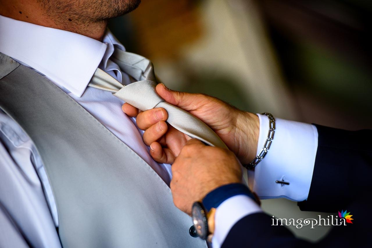 Dettaglio del nodo alla cravatta dello sposo durante la preparazione