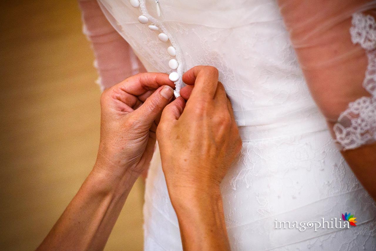 Dettaglio dell'allacciatura dell'abito nuziale durante la preparazione della sposa