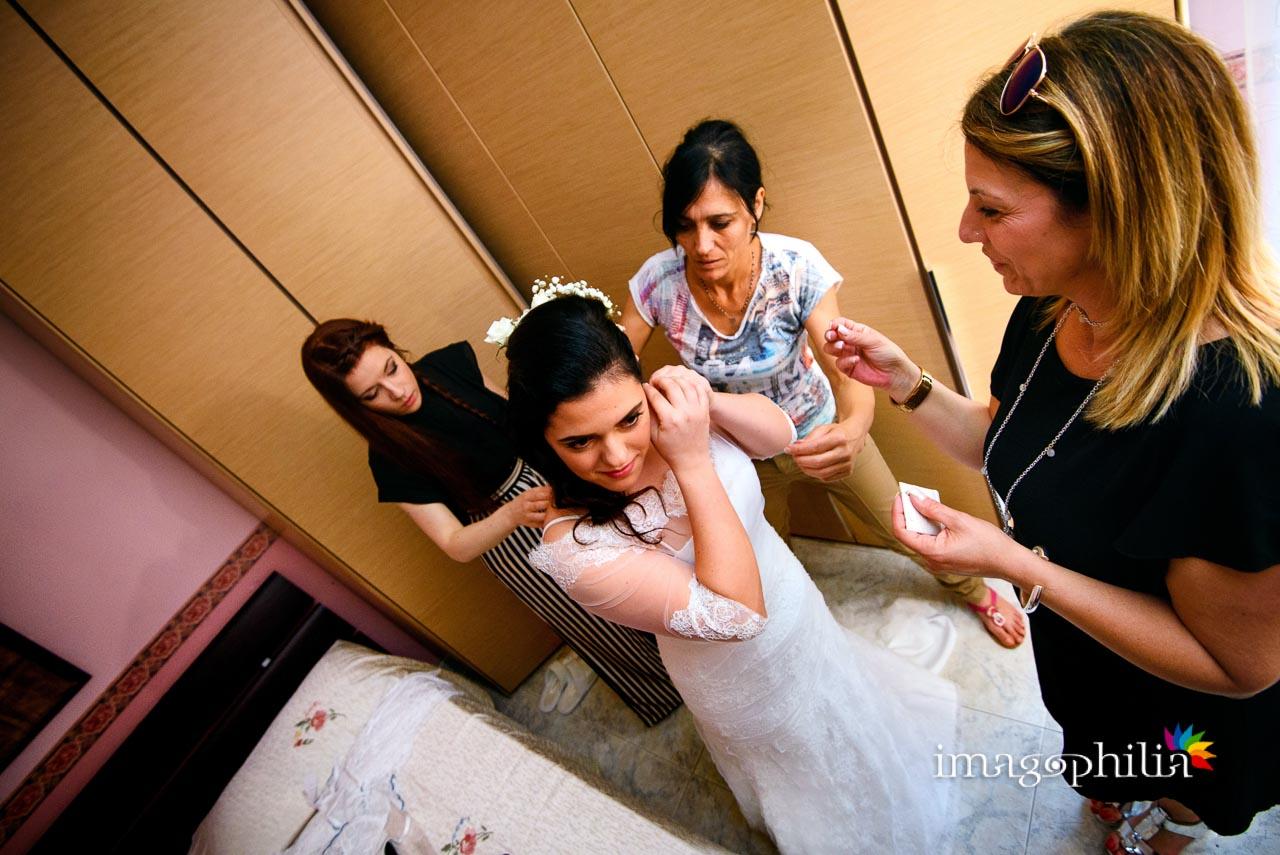 La sposa, accerchiata e assistita, termina i preparativi