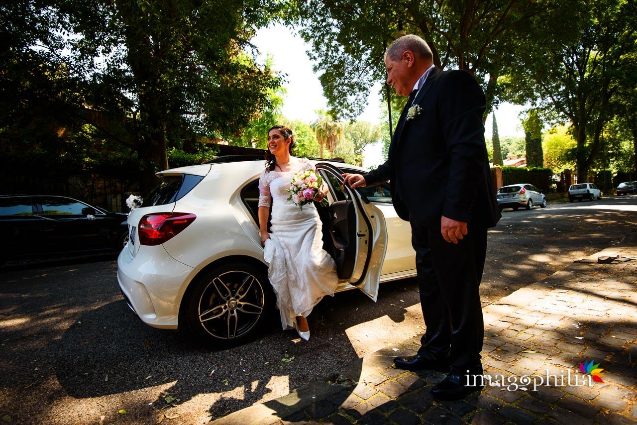 La sposa esce dall'auto, accompagnata dal papà, prima di entrare nel Complesso Vignola Mattei (Chiesa sconsacrata di Santa Maria in Tempulo a Caracalla, Roma)