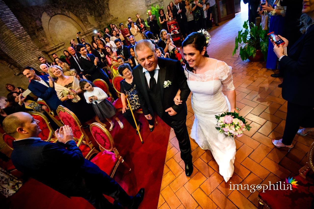 Ingresso della sposa a braccetto col papà durante il matrimonio civile nel Complesso Vignola Mattei (Chiesa sconsacrata di Santa Maria in Tempulo a Caracalla, Roma)