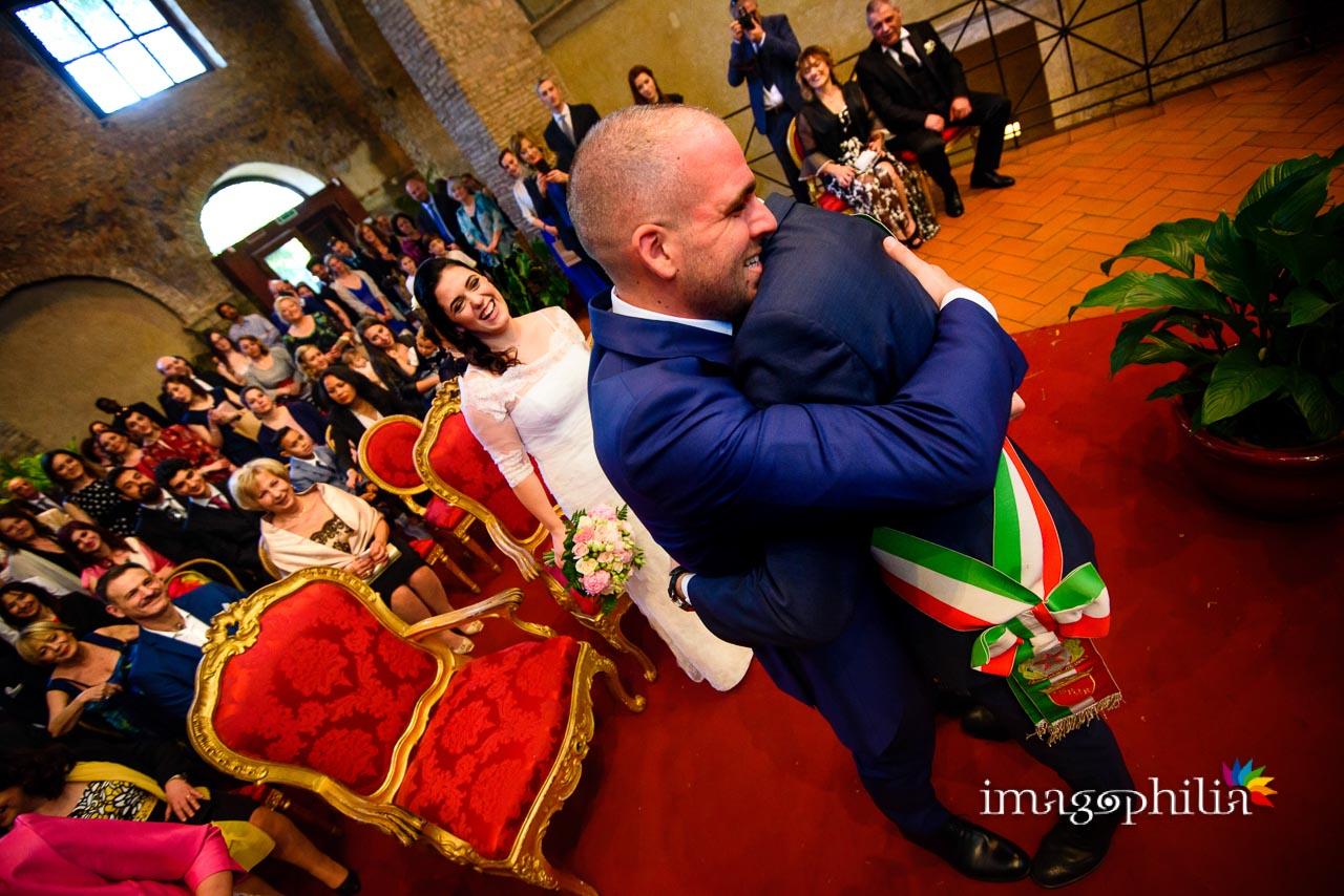 La sposa e la sala assistono all'abbraccio tra lo sposo e l'amico-celebrante durante il matrimonio civile nel Complesso Vignola Mattei (Chiesa sconsacrata di Santa Maria in Tempulo a Caracalla, Roma)