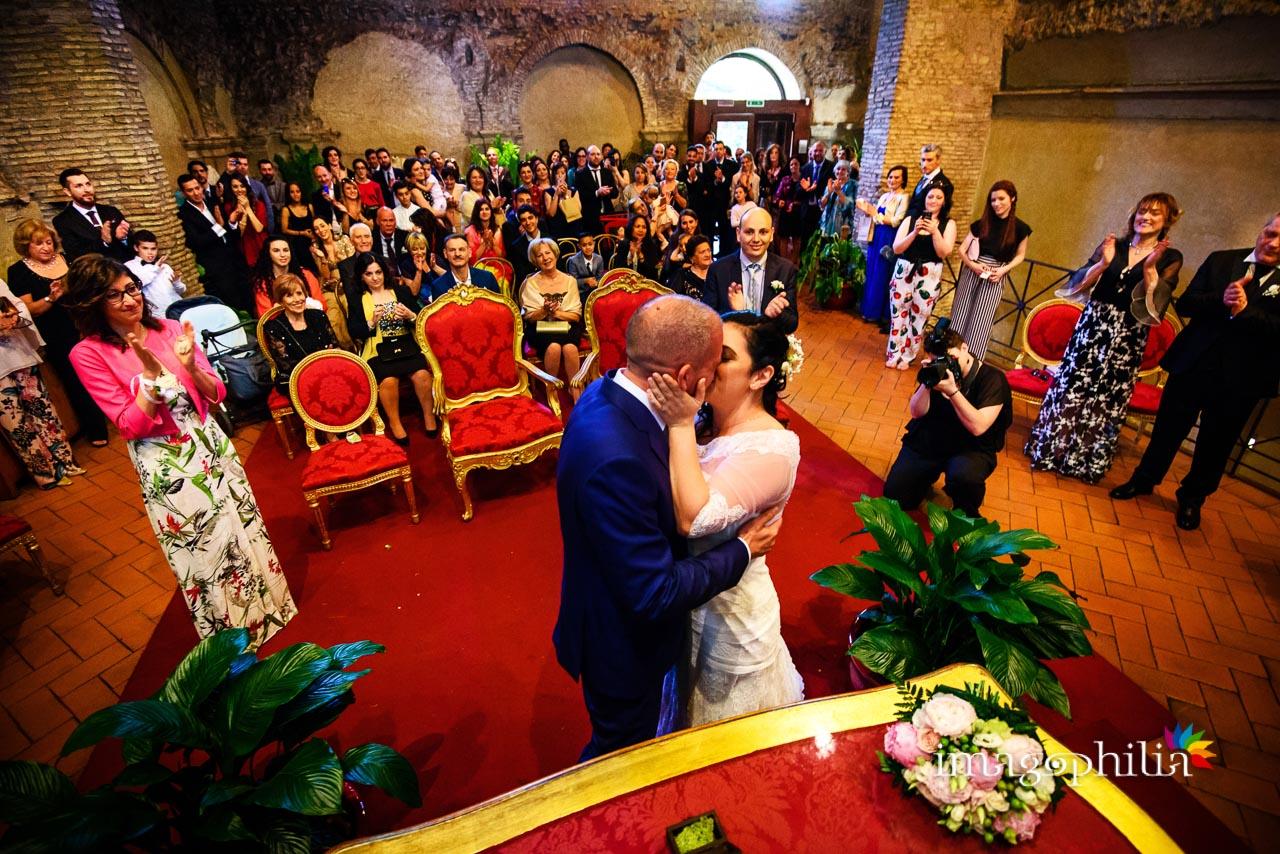 Finalmente si sente: «Può baciare la sposa!» durante il matrimonio civile nel Complesso Vignola Mattei (Chiesa sconsacrata di Santa Maria in Tempulo a Caracalla, Roma) / 2