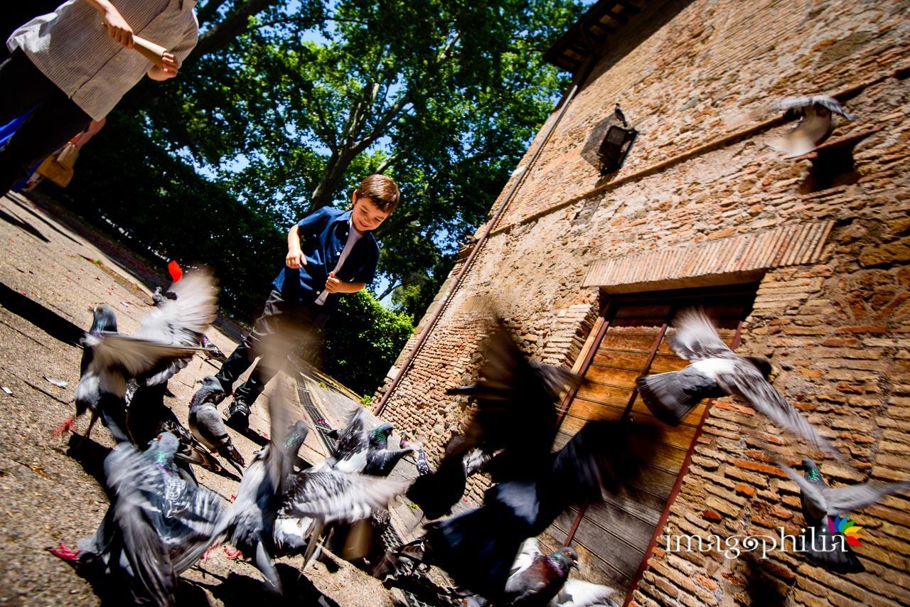 Un bambino si diverte a far volare i piccioni che beccano il riso subito dopo il matrimonio civile nel Complesso Vignola Mattei (Chiesa sconsacrata di Santa Maria in Tempulo a Caracalla, Roma)