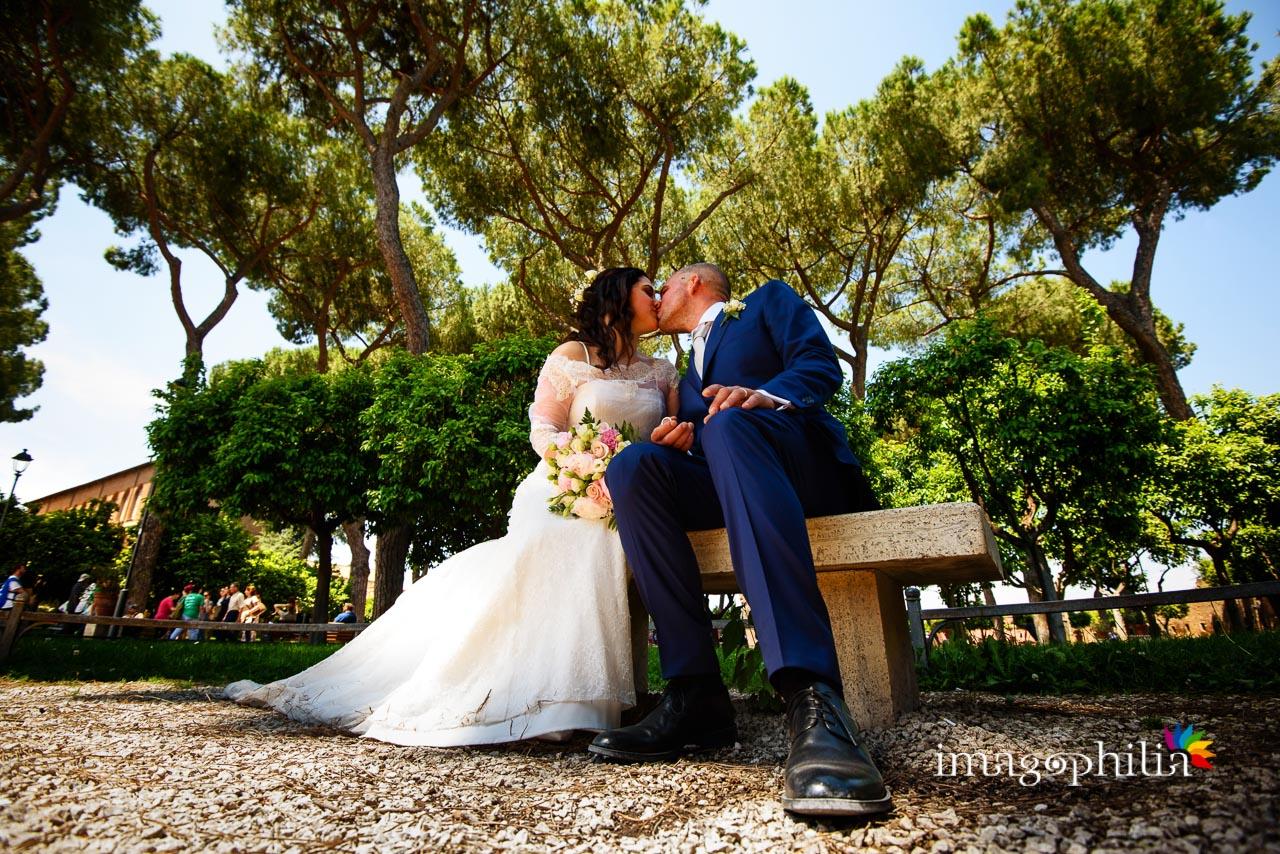 Bacio tra gli sposi su una panchina al Giardino degli Aranci sull'Aventino a Roma