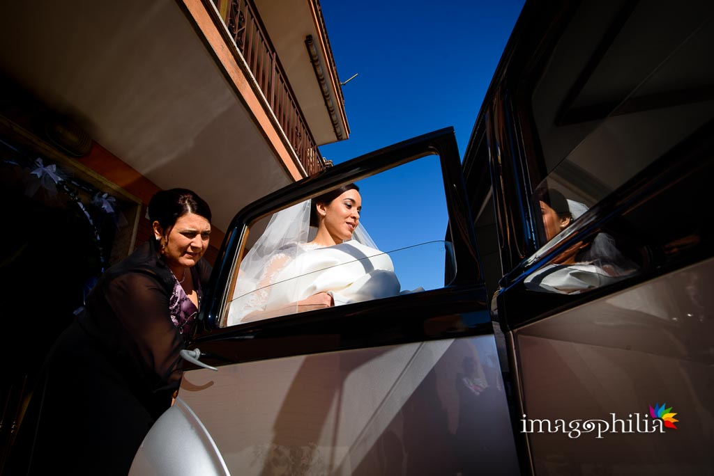 La sposa sale in automobile assistita dalla mamma