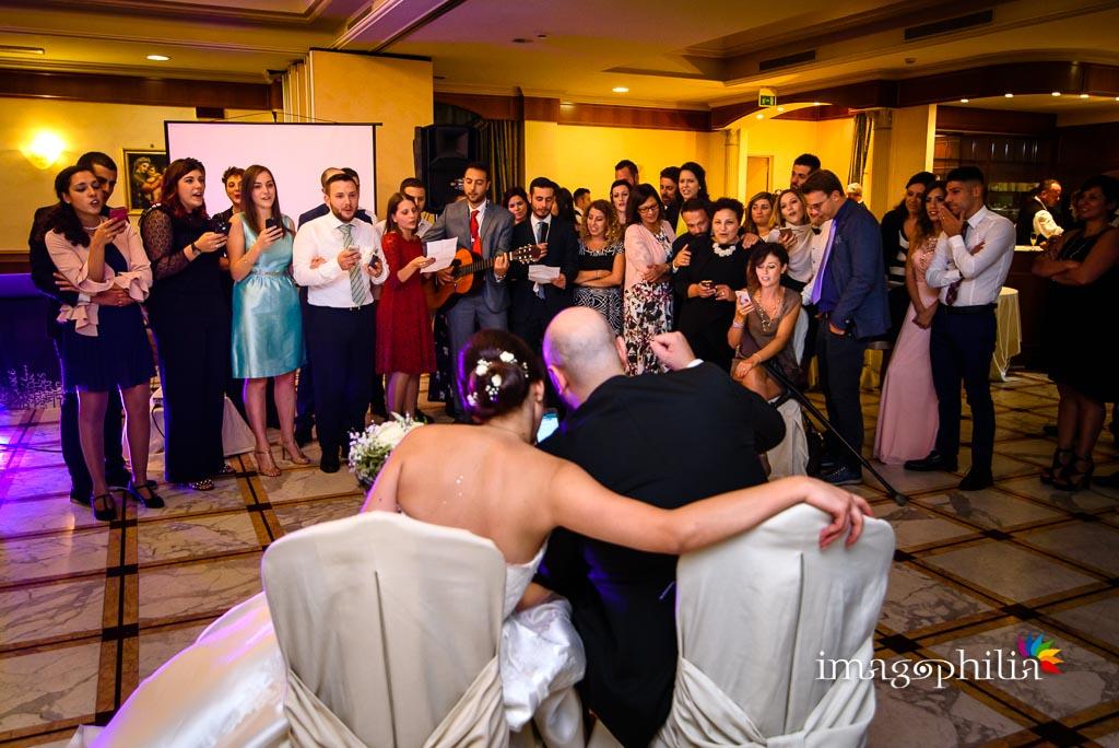 Gli amici della comunità cantano e suonano una canzone scritta per gli sposi al termine del ricevimento da Benito al Bosco, Velletri