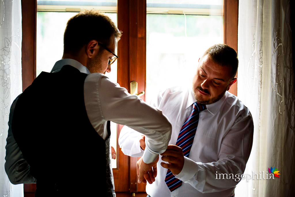 Il testimone aiuta lo sposo nella preparazione