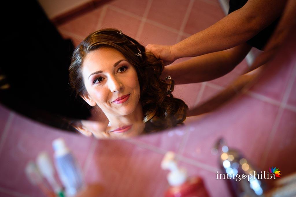 La sposa riflessa allo specchio durante l'acconciatura dei capelli