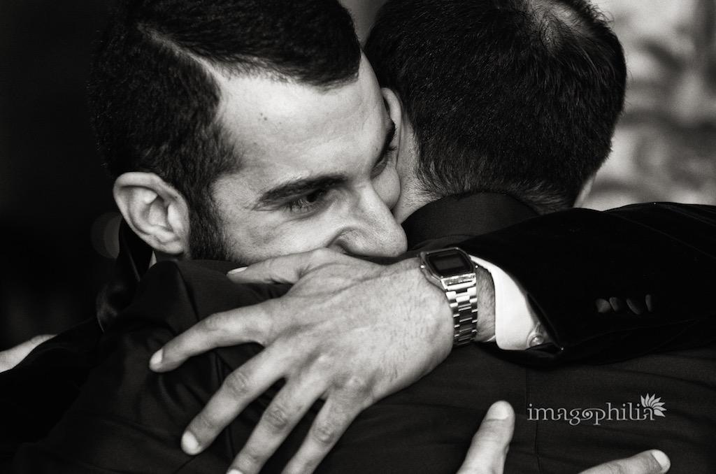 Abbraccio tra neocognati subito dopo il matrimonio nella sala da pranzo d'estate all'interno di Palazzo Chigi ad Ariccia