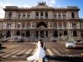 Gli sposi ritratti davanti al Palazzo di Giustizia a Roma