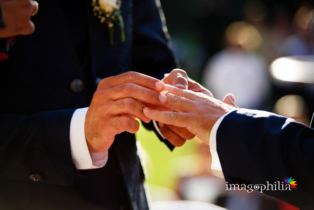 Scambio degli anelli nuziali tra gli sposi durante il matrimonio laico-umanista a Villa Gianni, Roma