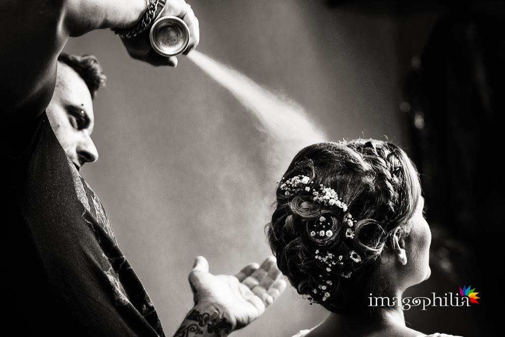 Il parrucchiere cosparge di lacca l'acconciatura della sposa