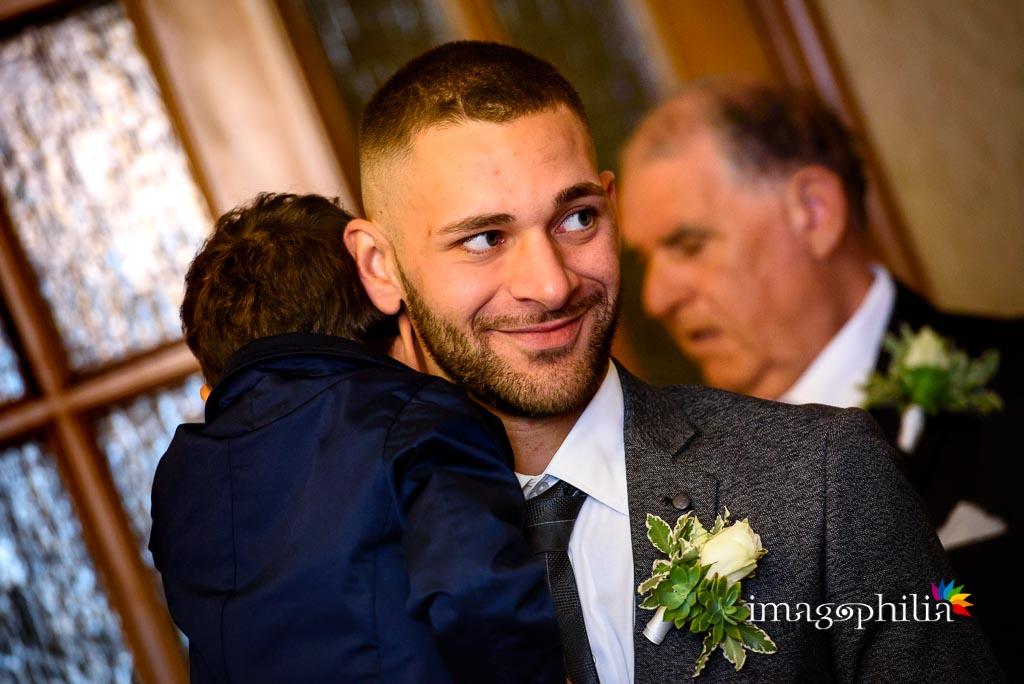 Un figlio della sposa ne tiene in braccio un altro