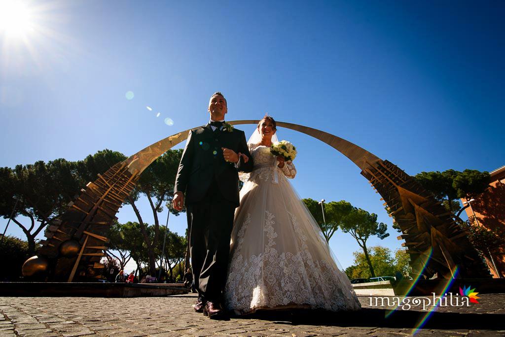 """Gli sposi """"trionfano"""" sotto un arco a Tivoli, subito prima della sessione esterna a Villa d'Este"""