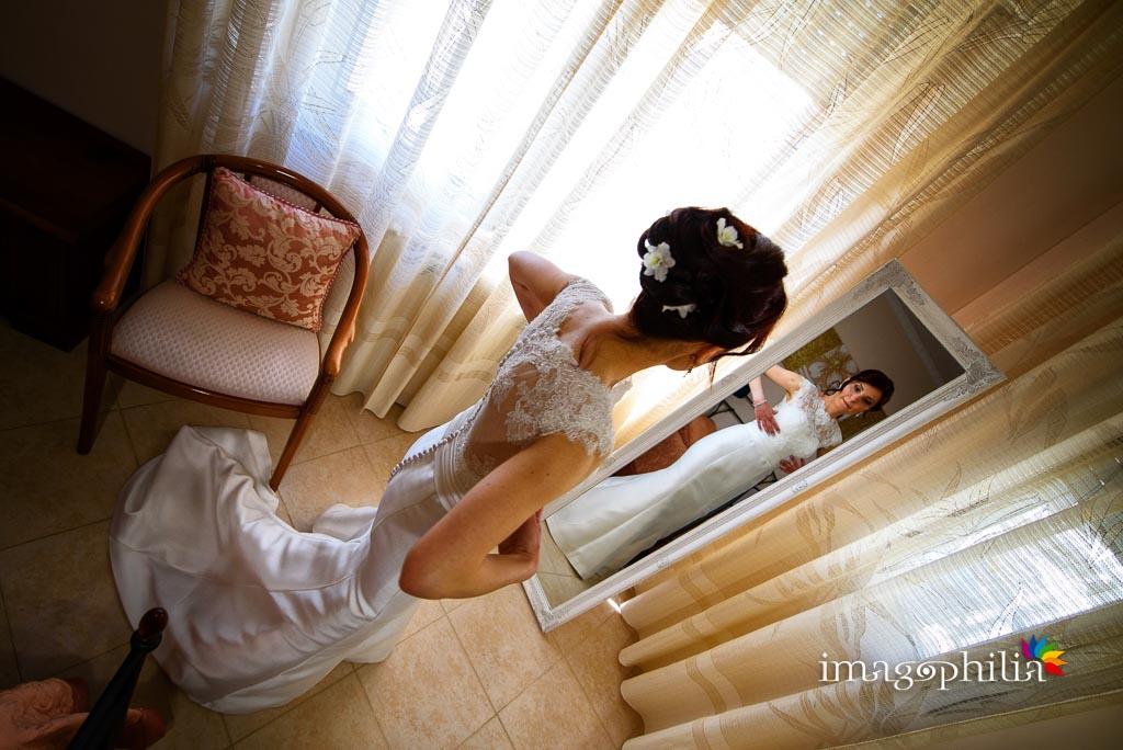 La sposa si guarda allo specchio al termine della preparazione a casa