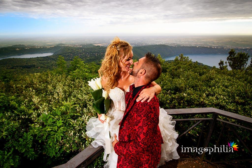 Bacio tra gli sposi sulla Via Sacra a Monte Cavo e, sullo sfondo, la vista mozzafiato sui laghi dei Castelli Romani (Lago Albano e Lago di Nemi)