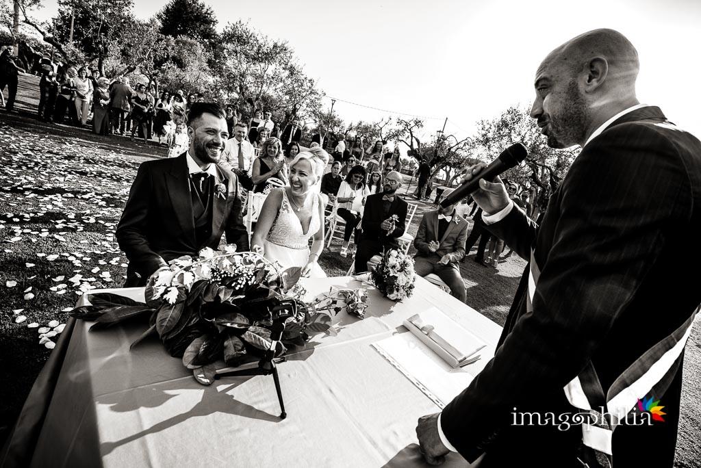 Sguardi e ilarità tra gli sposi durante le nozze sul prato del Borgo della Cartiera Pontificia / 1