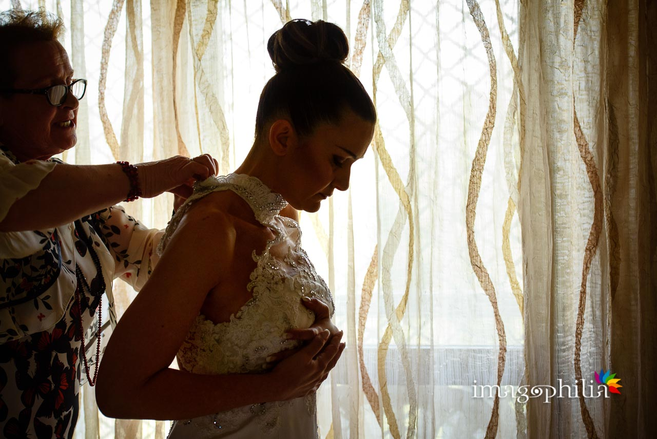La sposa in controluce è assistita nella vestizione