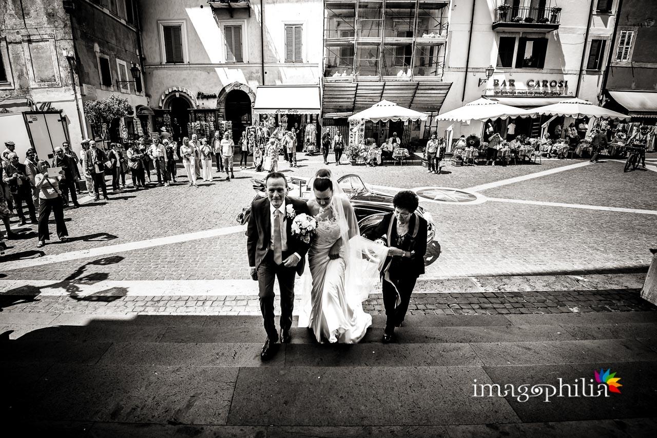 La sposa accompagnata dai genitori sale la scalinata di San Tommaso con la piazza di Castel Gandolfo sullo sfondo