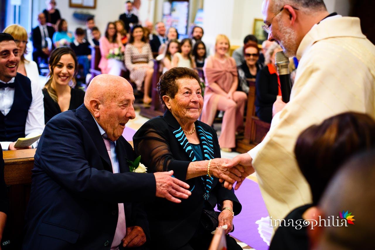 I genitori dello sposo stringono le mani al sacerdote durante il matrimonio nella Chiesa di San Tommaso da Villanova a Castel Gandolfo