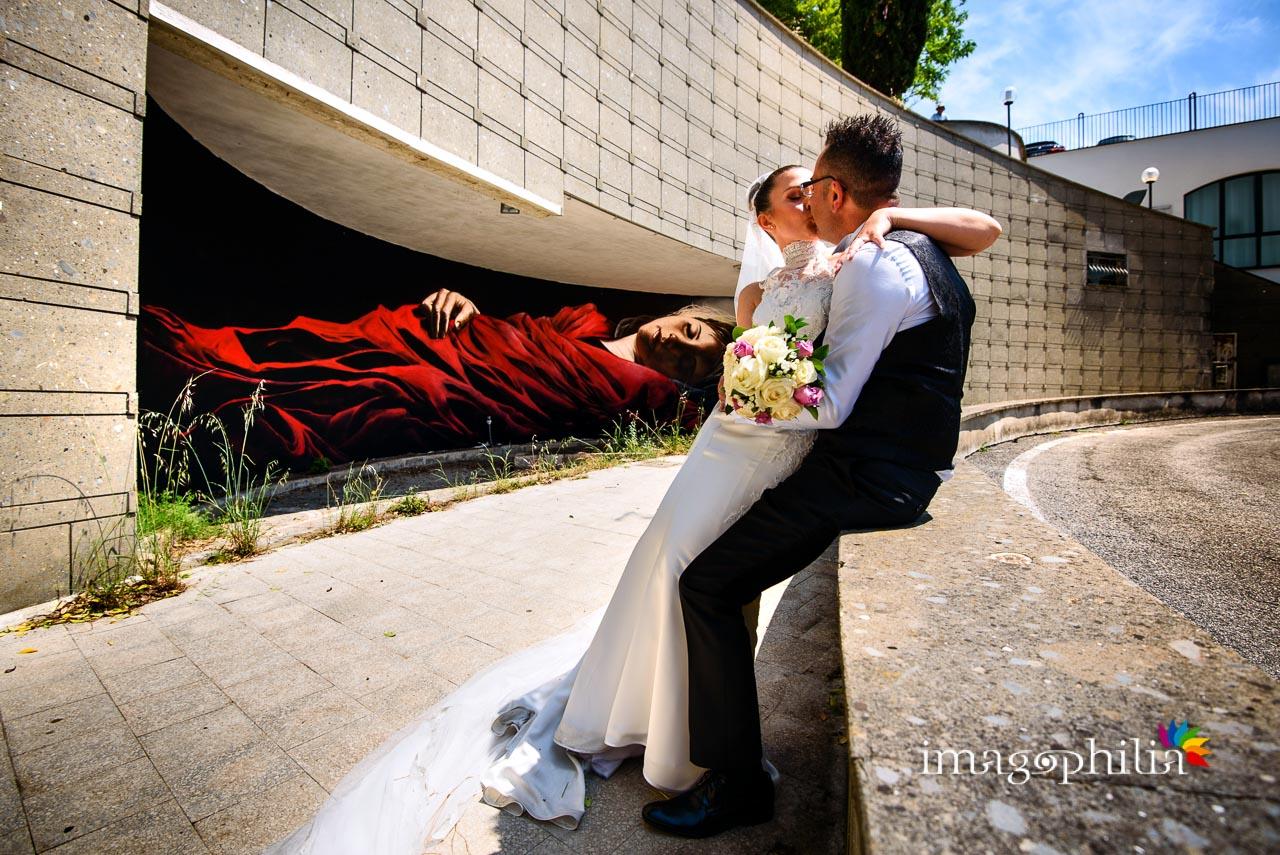 Gli sposi si baciano tra i murales alla stazione dei pullman di Castel Gandolfo