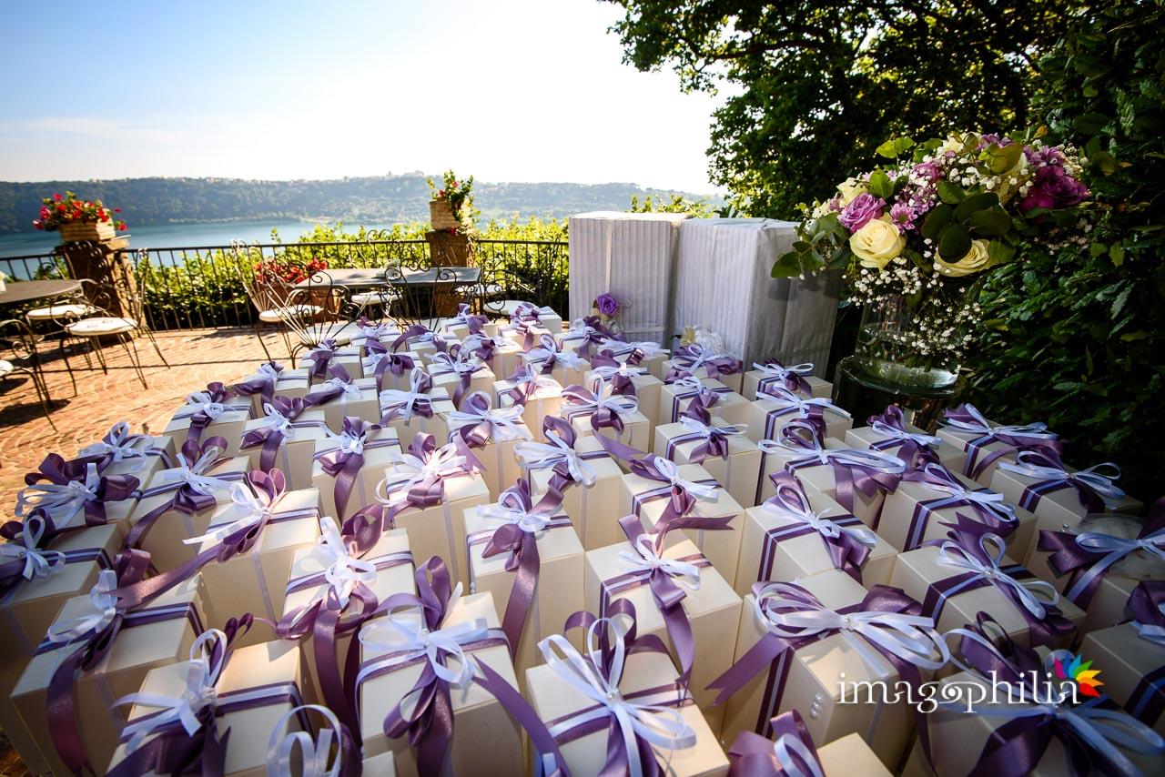 Bomboniere in prospettiva con in Lago Albano sullo sfondo durante il ricevimento di matrimonio a Villa Pocci (Marino, Via dei Laghi)